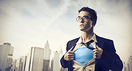 Young businessman showing the superhero suit under his shirt wit